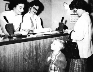 Shirley Nelson, at Central Desk in the Pittsburg clinic, has a word with Kenneth, 4, while Kathie Mendoza makes an appointment for his Ma - Mrs. A. N. Franklin. KP Reporter, 1962