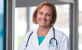Woman physician Shannon Garton, MD, in a lab coat and smiling