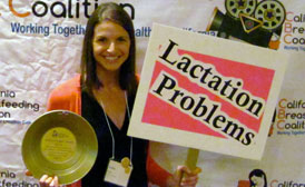 Woman recieving an lactation awareness award holding a gold pan, which is the award, and a sign which says, lactation problems