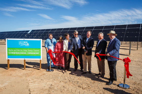 Ribbon cutting for new solar farm in Riverside county with a group of 7 people lined up and solar panels in the background