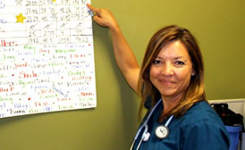 Shelia Chado, a Kaiser Permanente primary care Licensed Practical Nurse points to a chart at a meeting