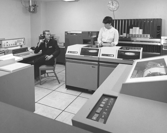 1964 image of a man and woman surrounded by large computers from the time.