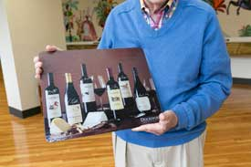 Man holding glass cutting board with wine bottle images