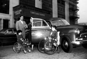 1952 image of a station wagon with a man and a woman standing next to the car along with two children in wheelchairs.