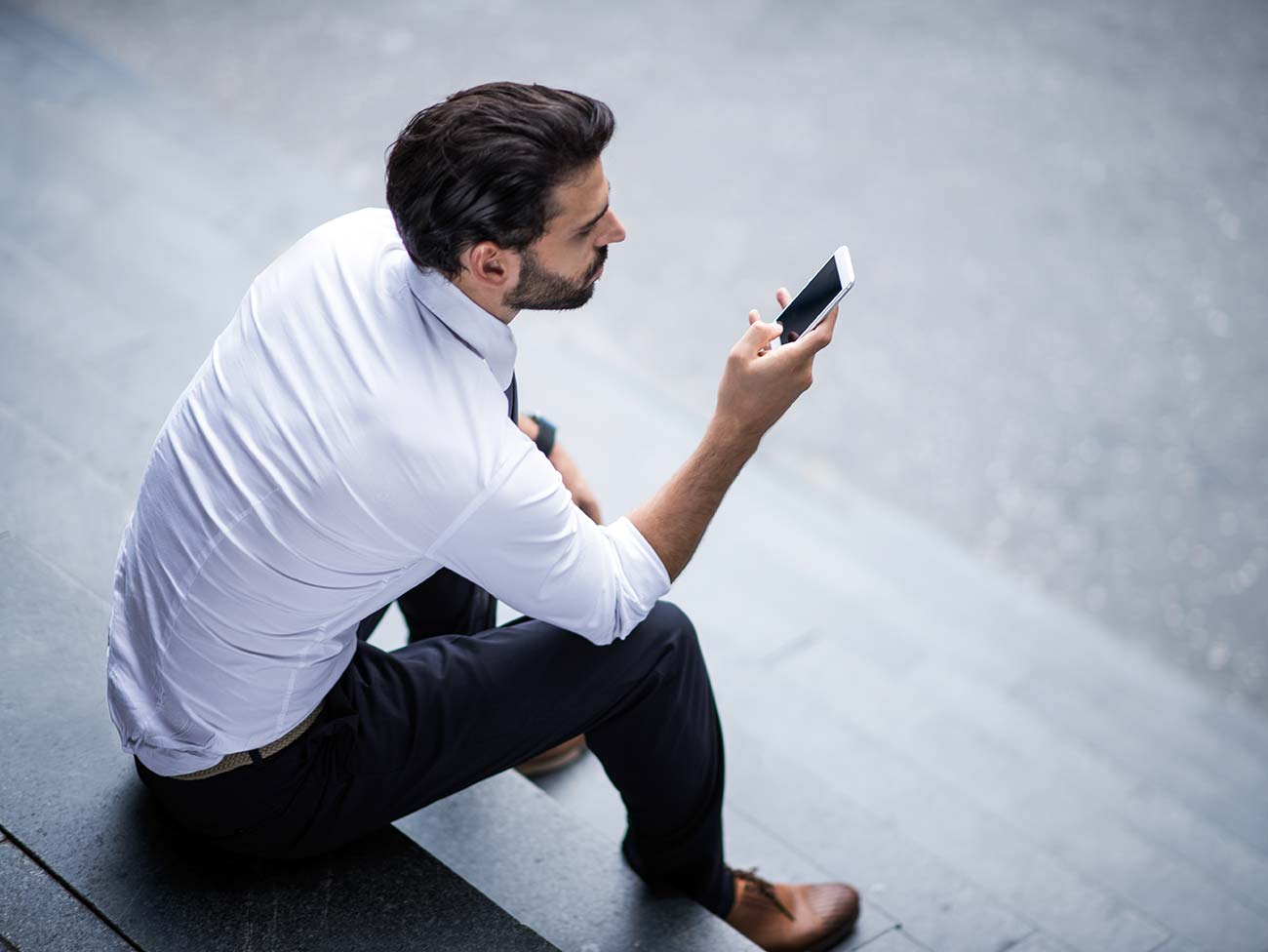 Young businessman with smart phone sitting on the stairs