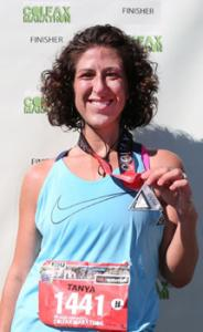 woman holding medal she won in running event