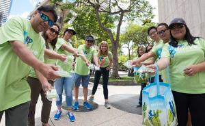 Kaiser Permanente Hawaii employees wearing bright green t-shirts, handing out giveaways for a Start Steppin' walking event