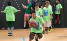 photo of young boy dribbling a basketball