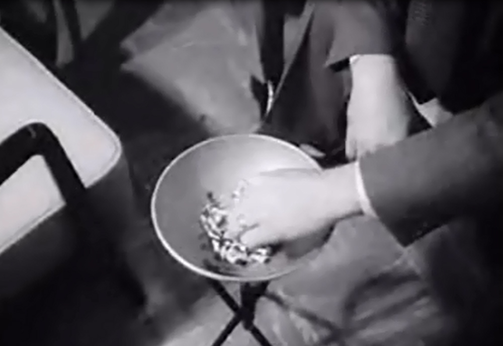 black and white image of a man's hand placing a cigarette into an ashtray
