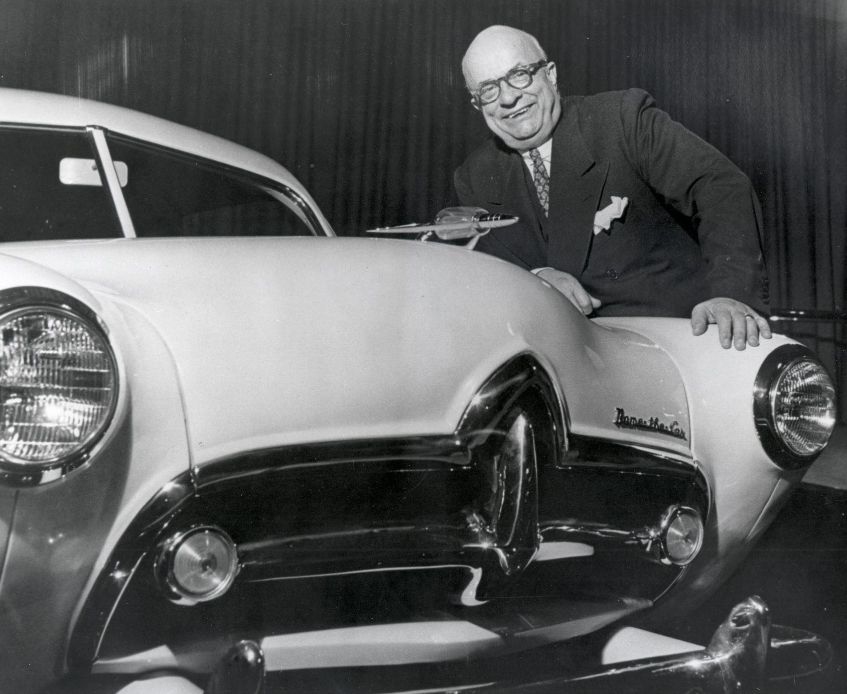 "Henry J. Kaiser with early model ""Henry J"" car before it was named - badge on hood says ""Name The Car."" 2/29/1950."