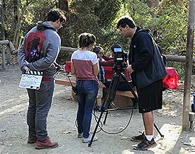 Two young men and a woman prepare to film a scene in a movie