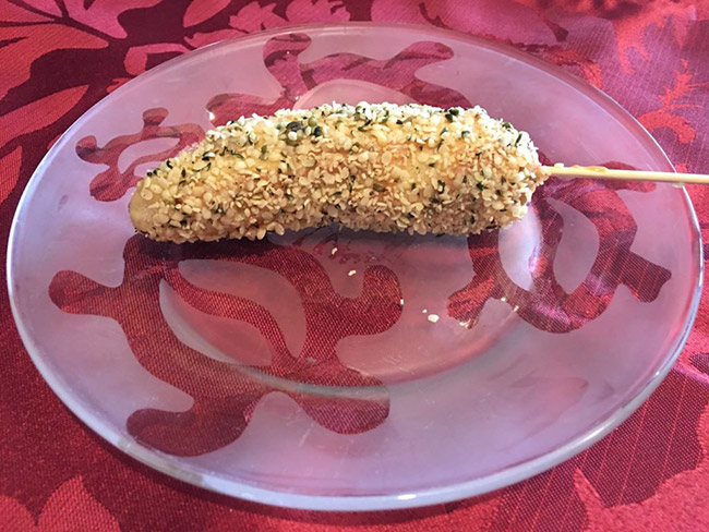 skewered banana coated with almond butter and covered with hemp seed and flaxseed meal
