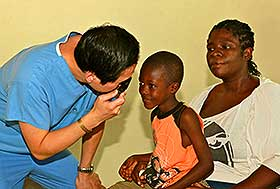 Dr. Maxwell Cheng examing a young Jamican boy's eye with mother looking on