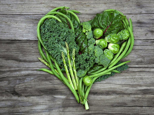 vegetable array of green beans, kale, asparagus, chard, brussels sprouts, and broccoli arranged to form the shape of a heart