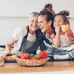 Mother, Grandmother and daughter smiling and laughing in the kitchen.