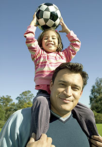 Man with his young daughter, holding up a soccer ball, on his shoulders