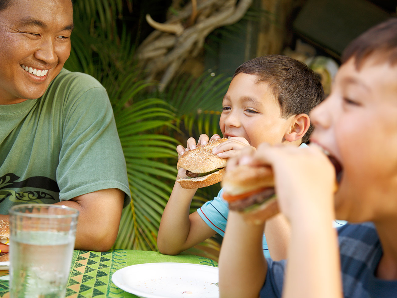 man seated at table smiling and looking toward 2 young boys who are eating sandwiches