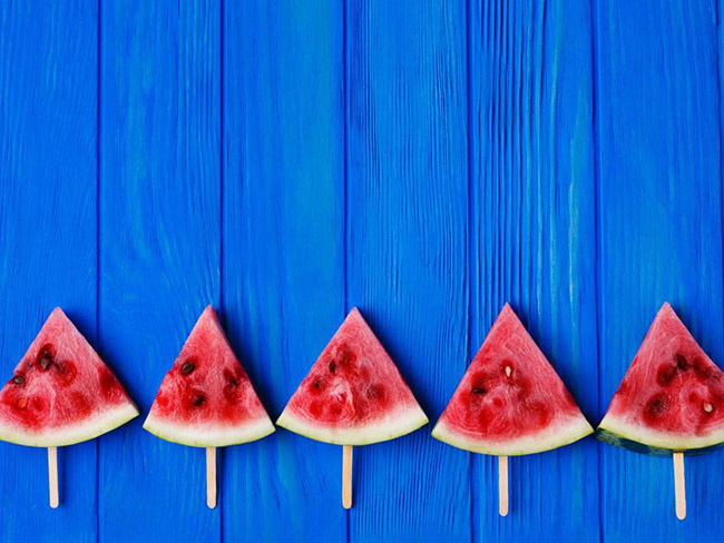 5 triangular watermelon slices with popsicle sticks pierced through the rinds