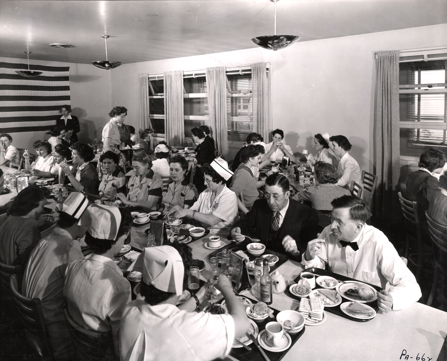 Black and white photo of Kaiser Oregonship staff cafeteria, with nurse in 1942.
