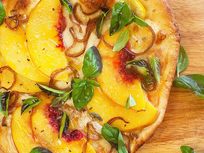 Top view of pizza topped with mozzarella, sliced peaches, caramelized onions and chopped fresh basil.