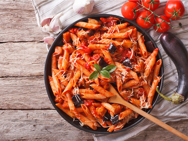 Penne pasta and vegetables in a large serving bowl with eggplant and tomatoes alongside.