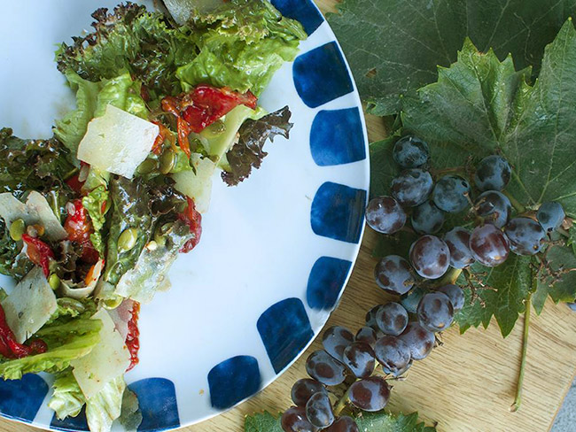 Salad arranged on a white and blue plate alongside a bunch of purple grapes.