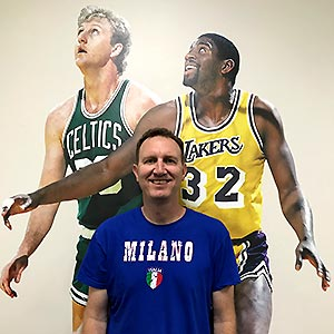 Michael Silverberg in front of a mural with NBA players Larry Bird and Magic Johnson
