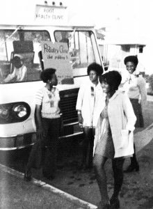 1970s era black and white photo of 4 members of Kaiser Black Student Nurses' Association standing in front of a mobile health van