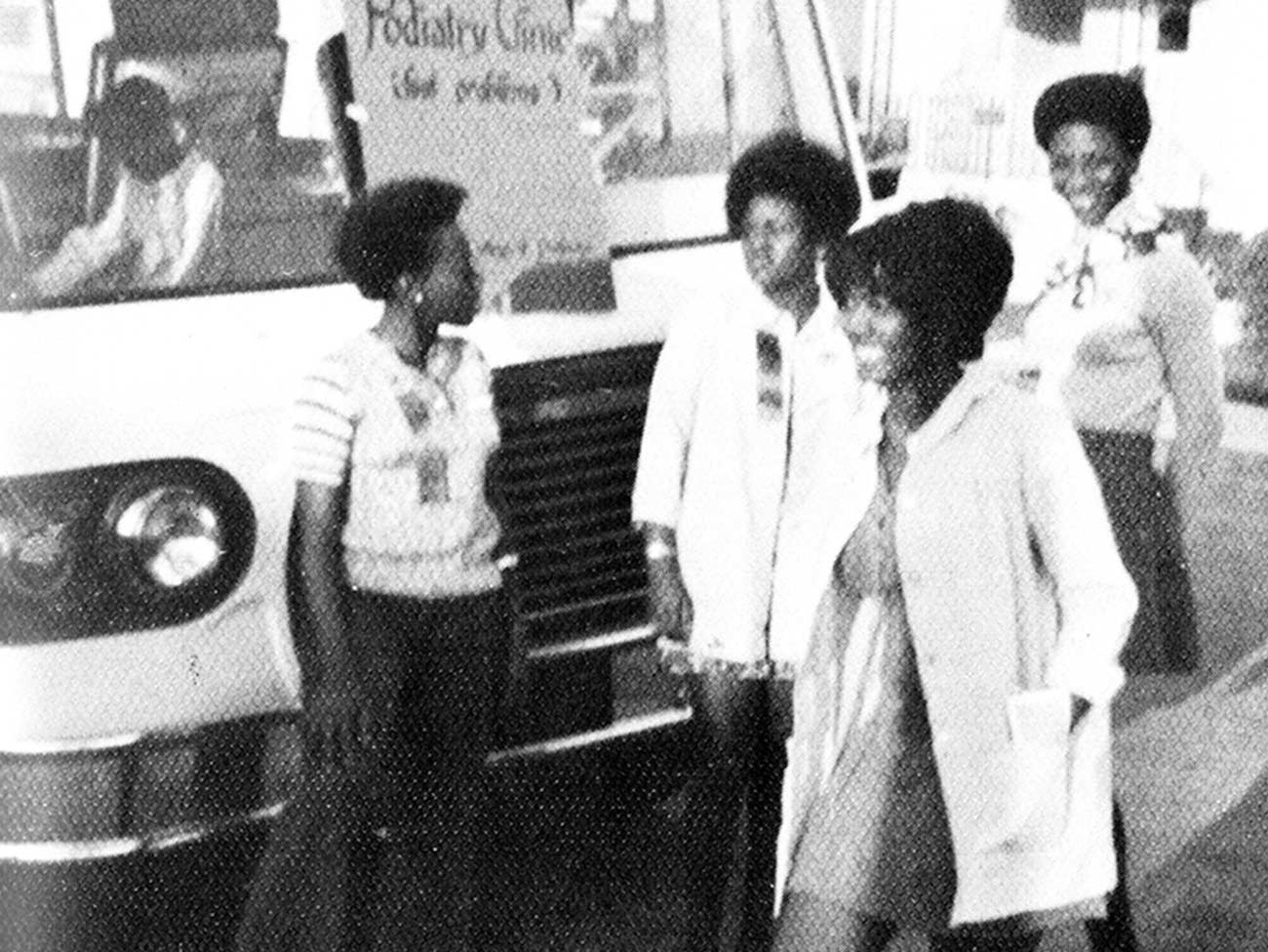 "4 young 70s era women nursing students standing in front of a large mobile health van with a sign that reads ""podiatry clinic"""