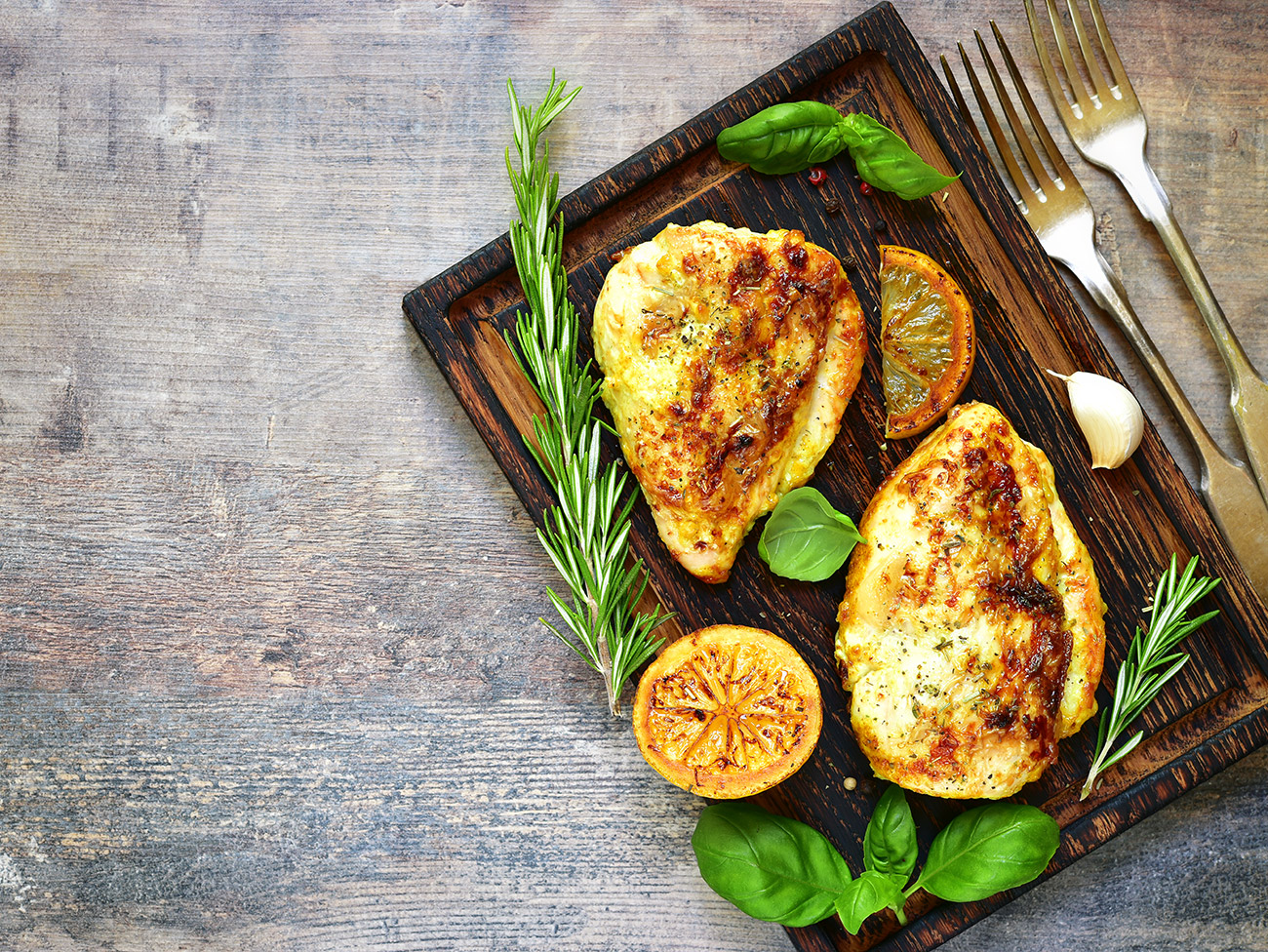 Two pieces of marinated chicken on wood board, with lemon slices and greens placed decoratively around chicken.