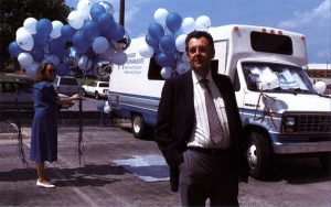 man wearing suit and tie standing in front of mobile health care van while woman in the background holds blue and white balloons