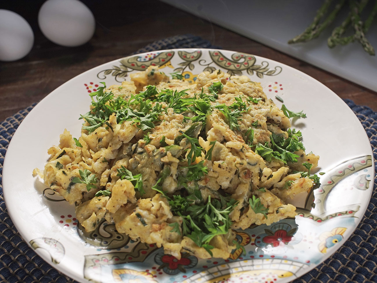 eggs scrambled with asparagus and spices, topped with fresh italian parsley