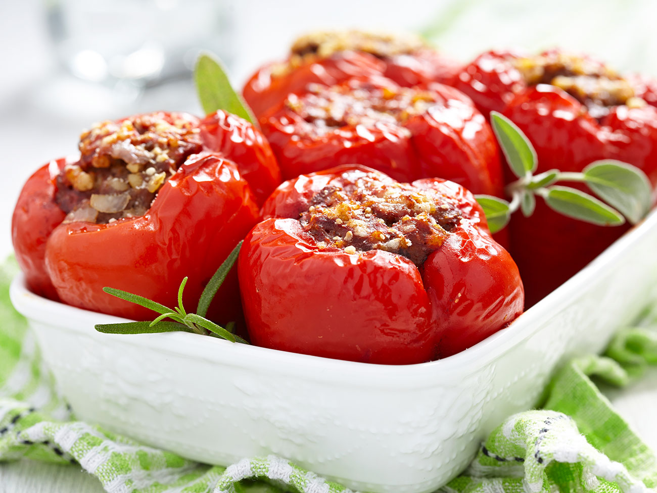 ceramic casserole dish with stuffed red bell peppers garnished with sage leaves