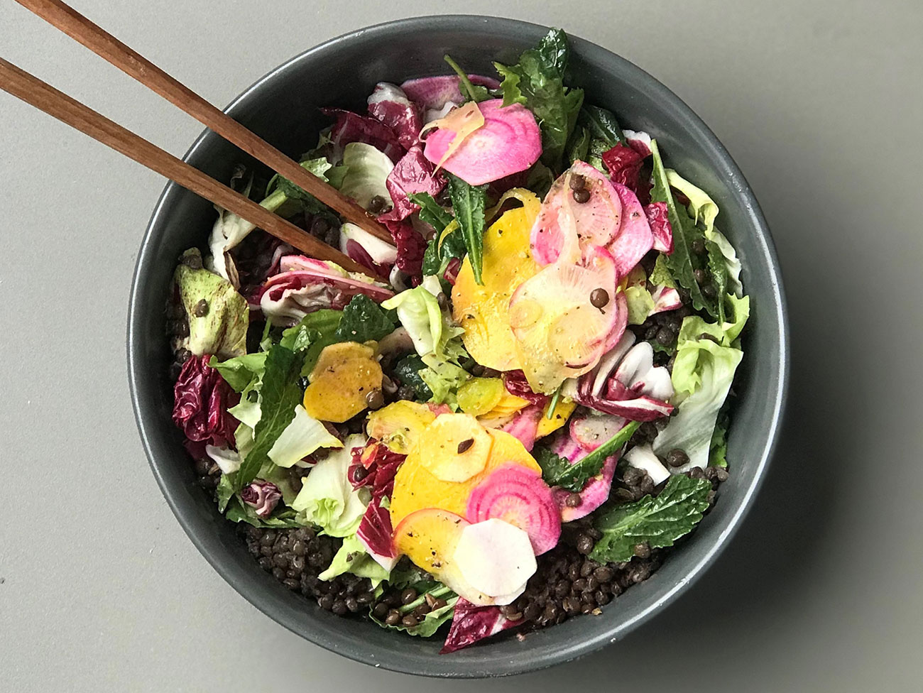 bowl of salad with lettuce, kale, sliced beets, radishes, and lentils