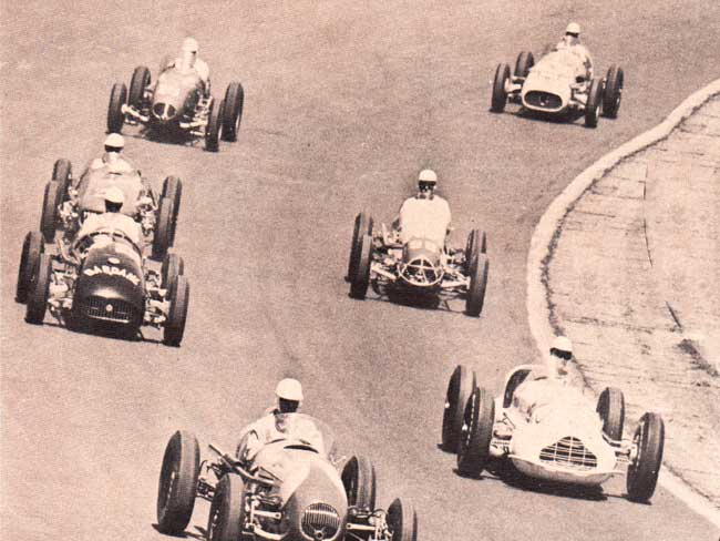 Black and white photo of racecars turning around a track in 1953