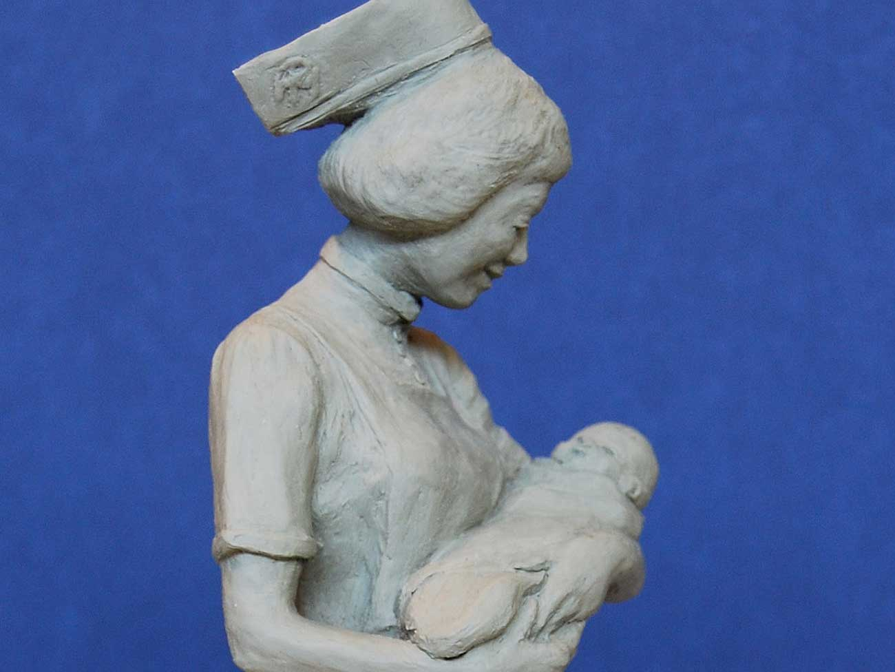 Clay model a nurse holding a baby in her arms.