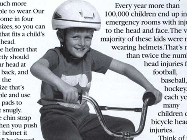 Newspaper clipping with a photo of a boy on a bicycle wearing a helmet