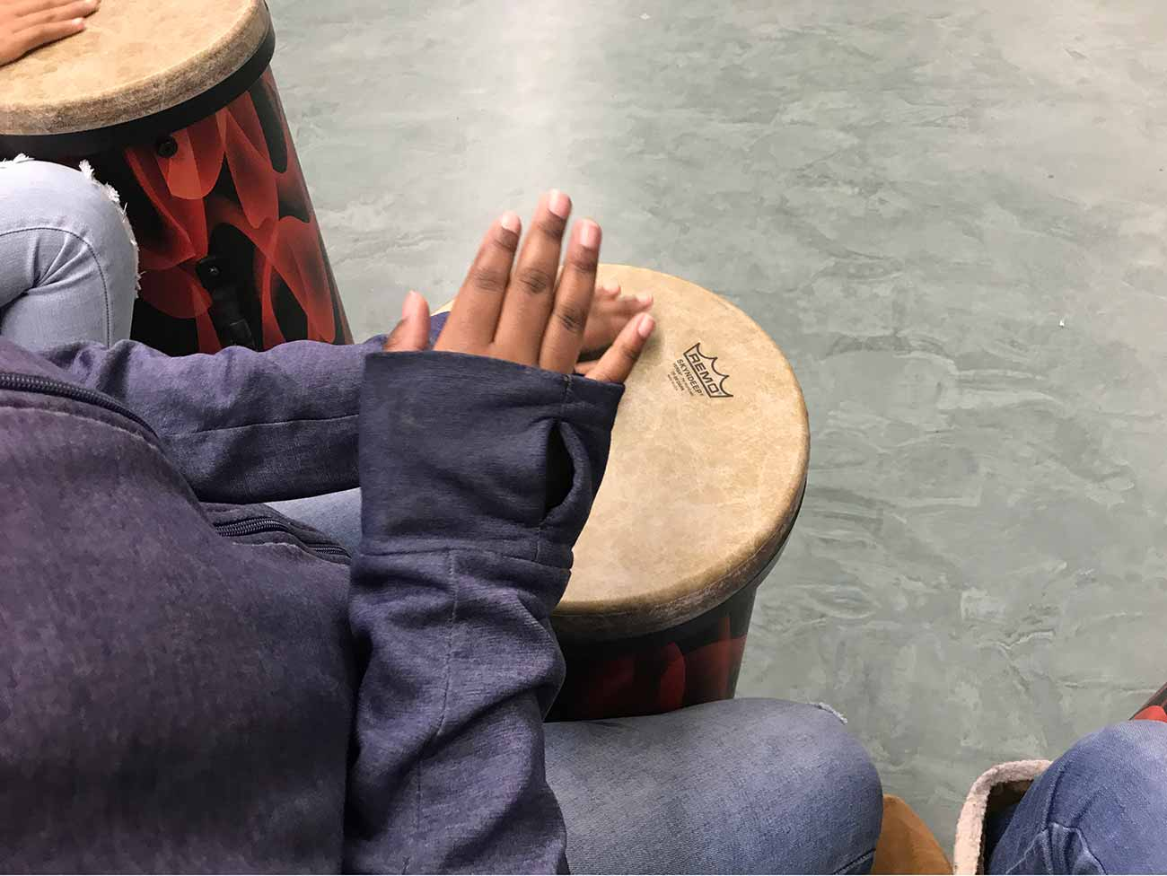 A child's hand on a small drum.