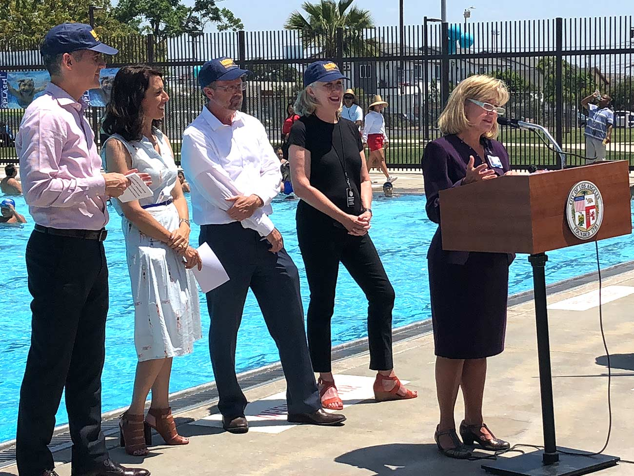 Woman standing at a podium, in front of a swimming pool, with several other people next to her listening to her speaking.