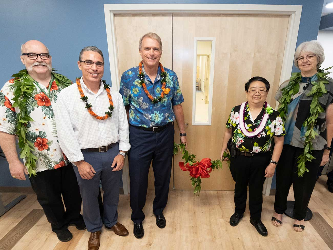 A group of people in Hawaiian shirts at a ribbon cutting ceremony.