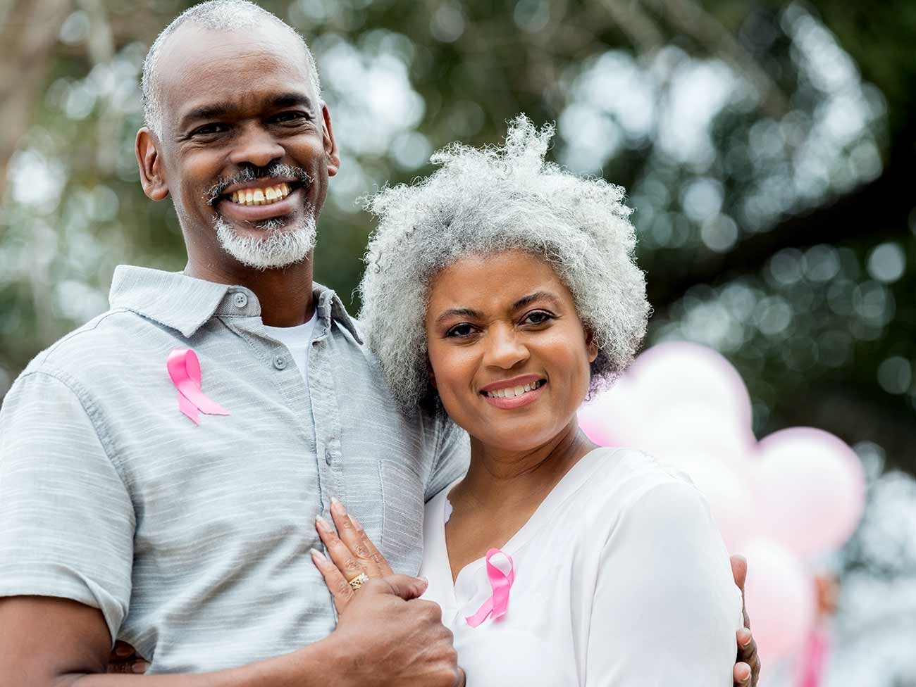 Smiling senior man and woman, both are wearing pink breast cancer awareness ribbons.