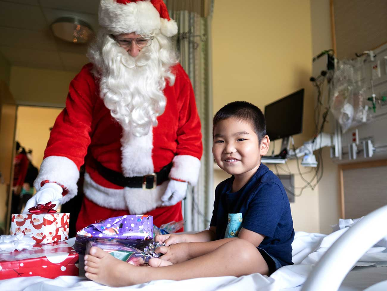 A smiling 4 year old boy in a hospital bed surrounded by gifts, Santa Claus is standing next to the bed.