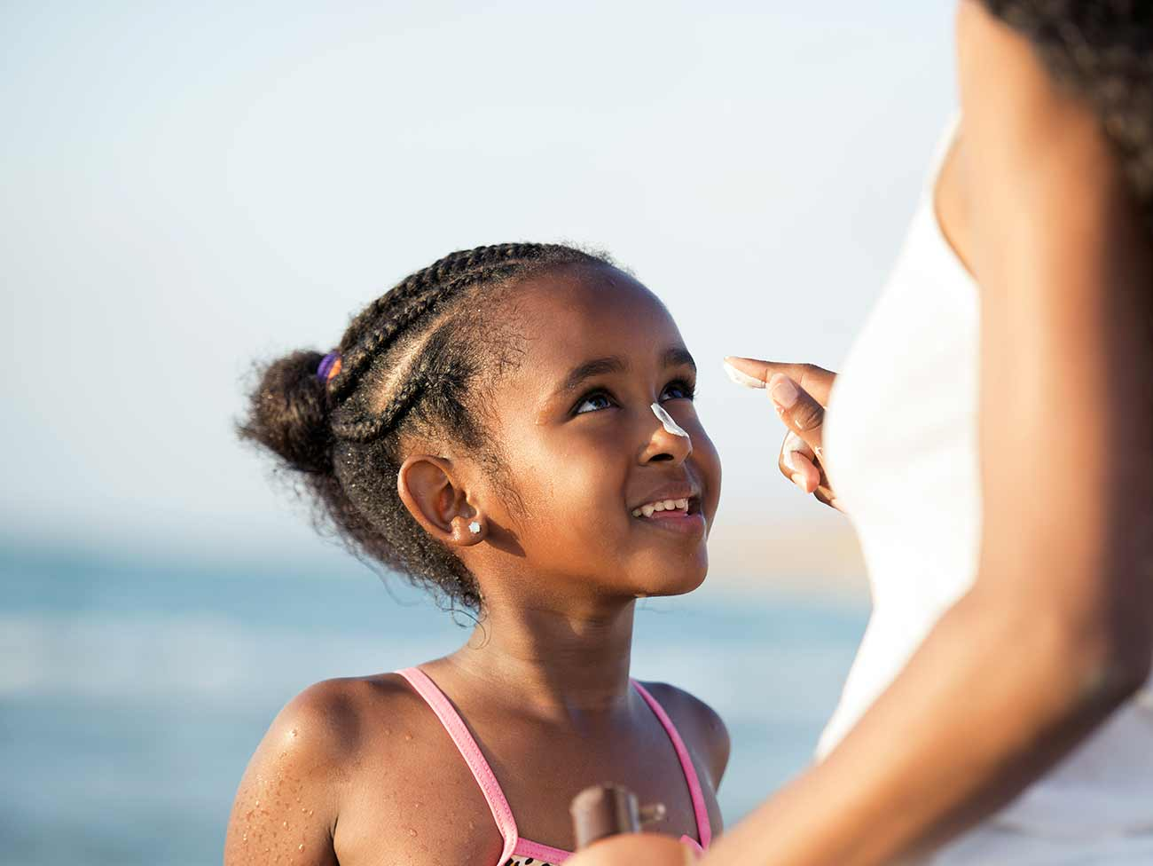 Mother applying sun protection cream to her young daughter on the beach.