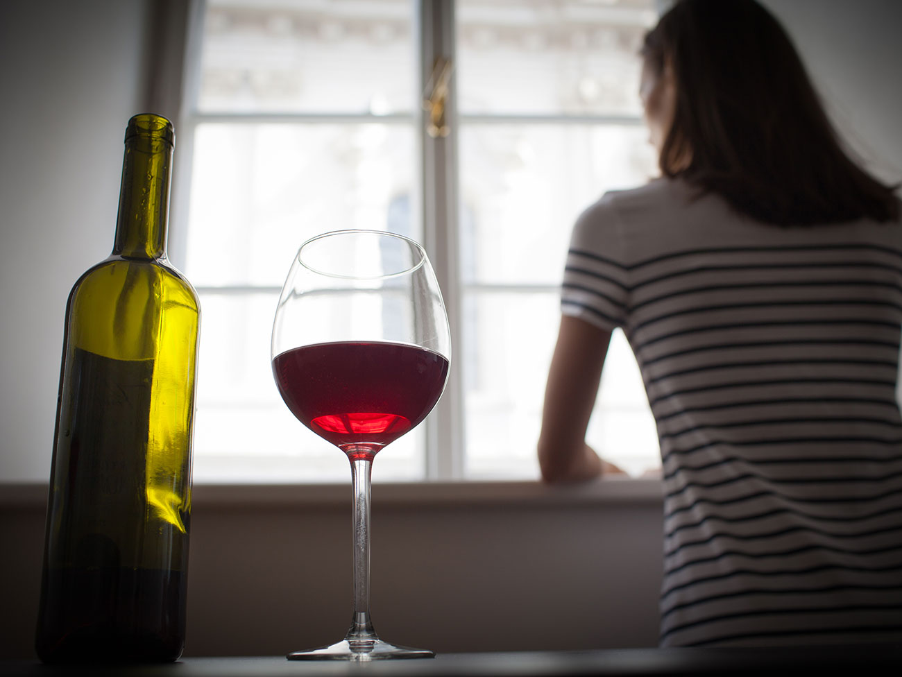 Woman drinking wine alone in a dark room