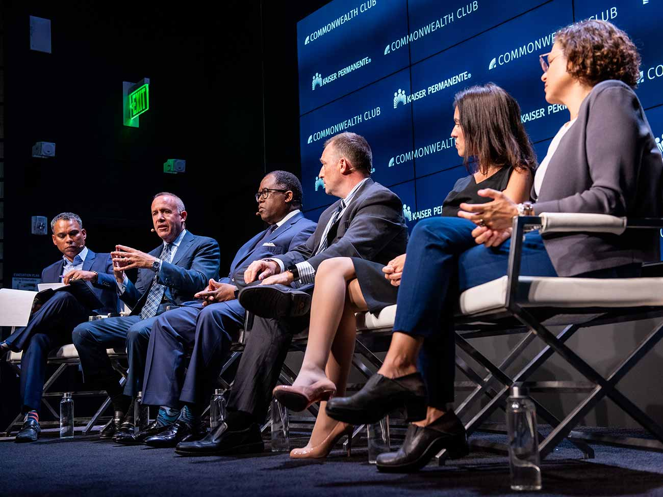 Panel of 6 individuals seated on stage in front of a screen with Kaiser Permanente and Commonwealth Club logos