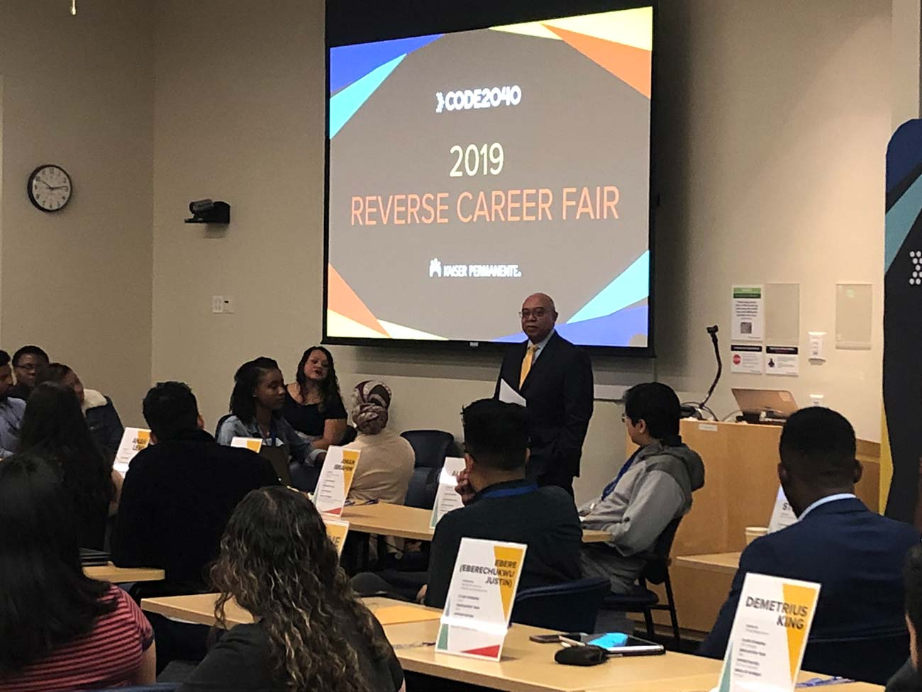 Dick Daniels speaking to a group of seated individuals in front of a screen that reads 2019 Reverse Career Fair