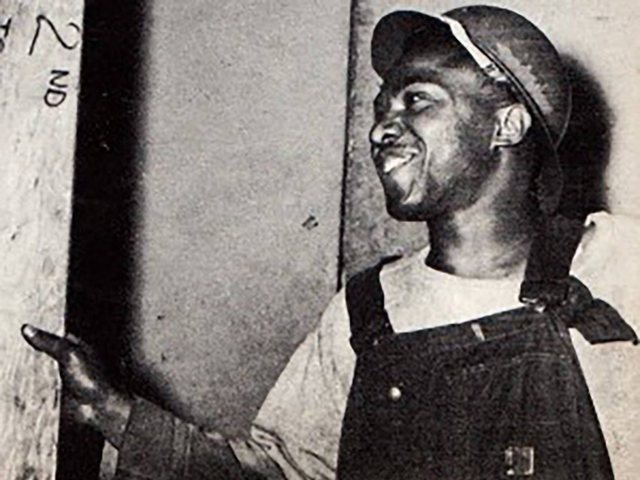 Black and white photo of Ralph Kinney wearing overalls and a hard hat