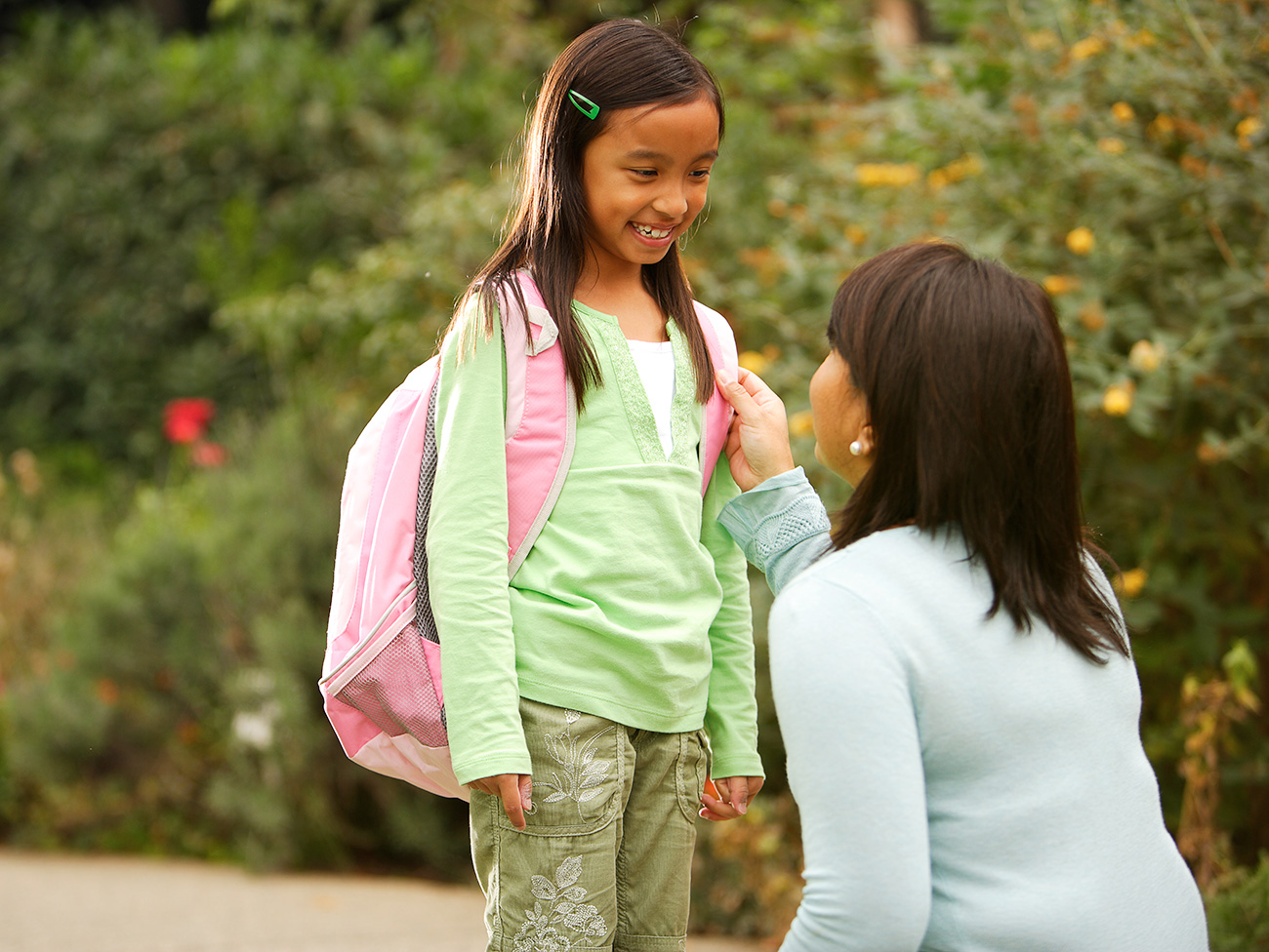 Child with backpack smiling at mother