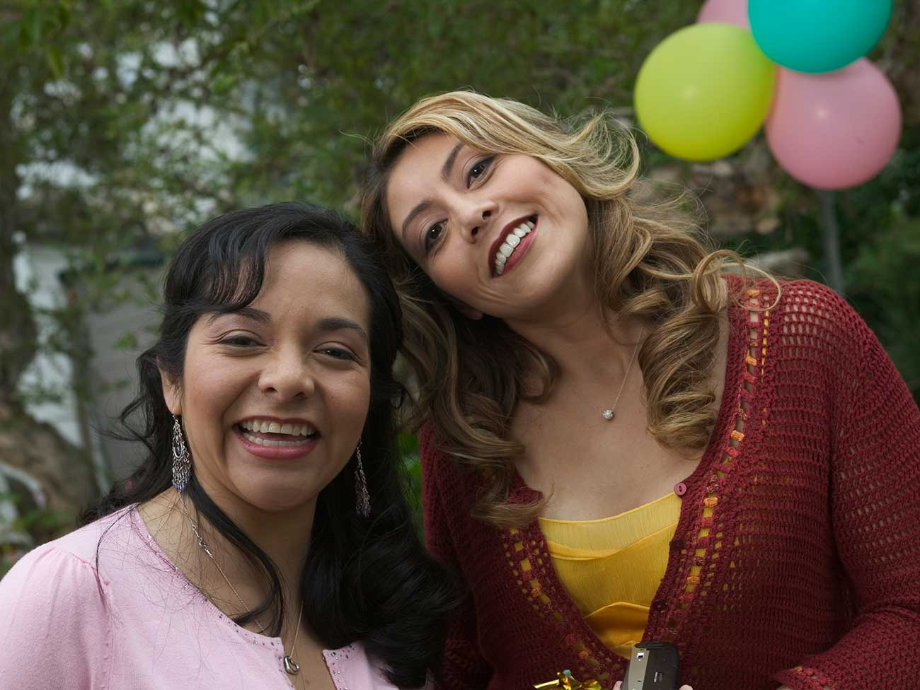 2 women in an outdoor setting looking at the camera and smiling with balloons in the background