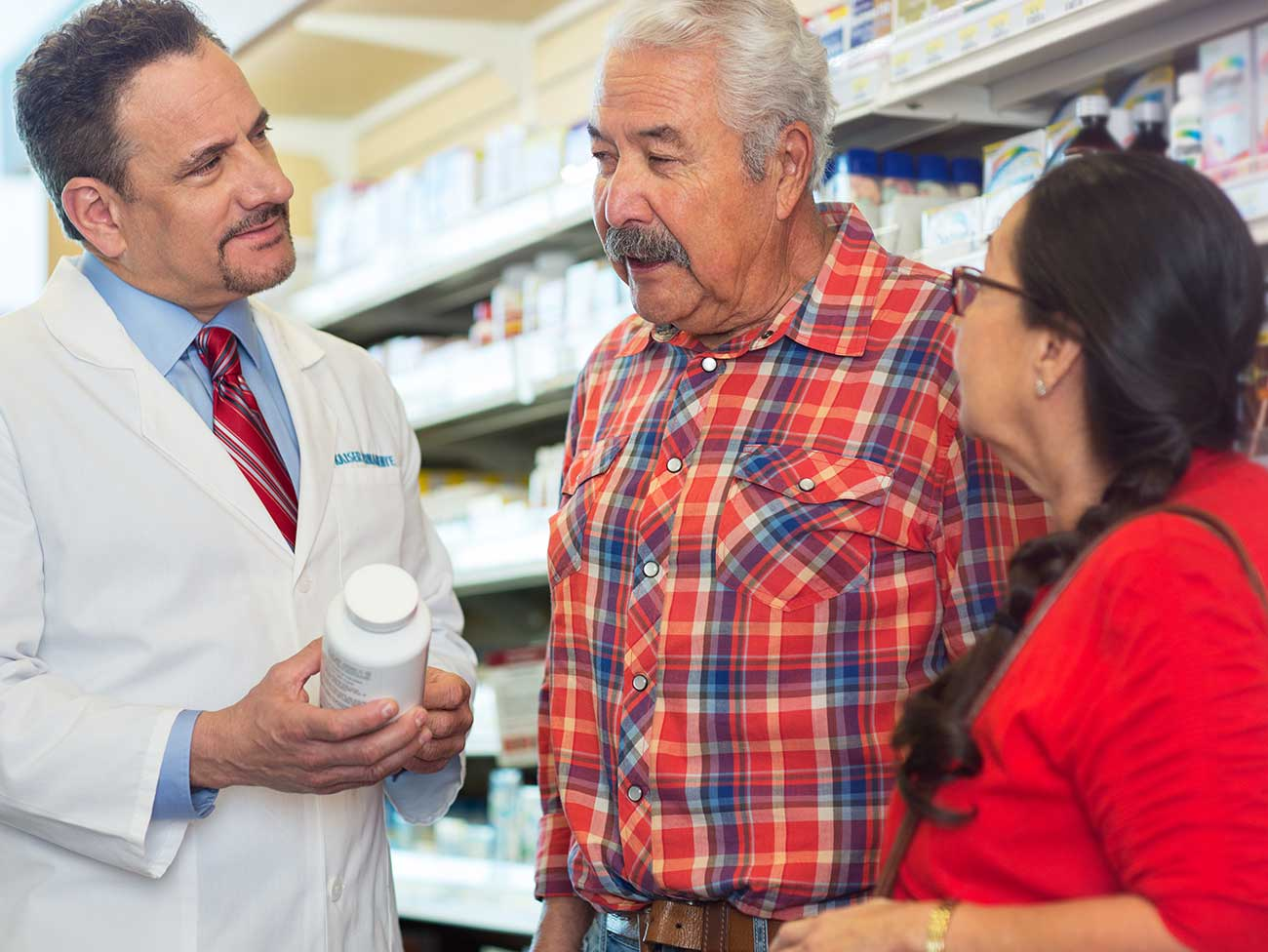 man wearing a white Kaiser Permanente labcoat speaking with an elderly couple in a pharmacy